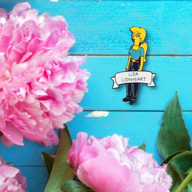 Simpsons Lisa Lionheart pin on on blue background with flowers