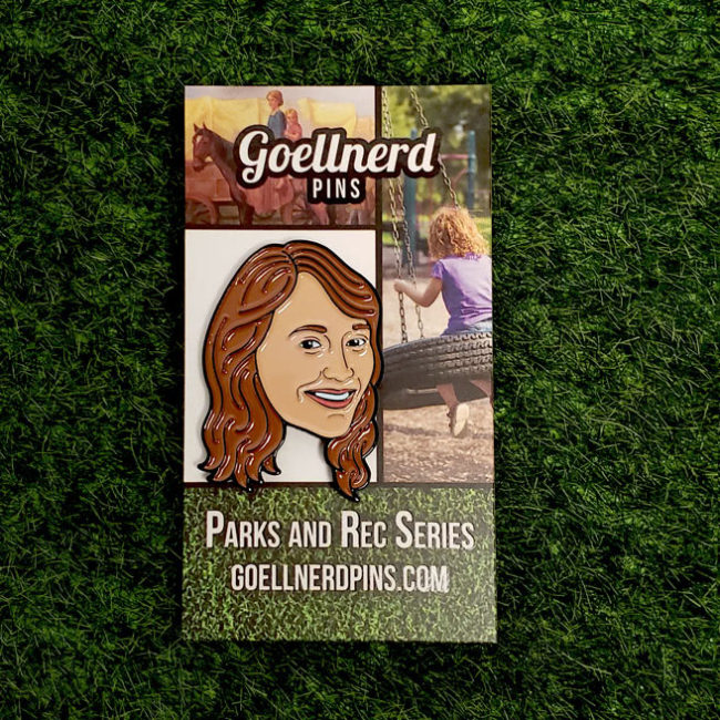 Ann Perkins Enamel Pin on a backing card in the grass
